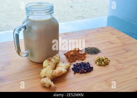 Chai Latte boisson maison chaude, avec toutes les épices utilisées, sur une planche à découper en bois.