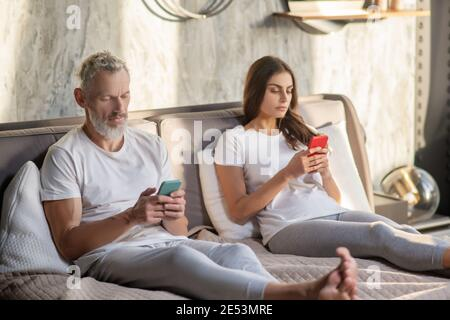 Homme et femme avec un smartphone assis sur le lit