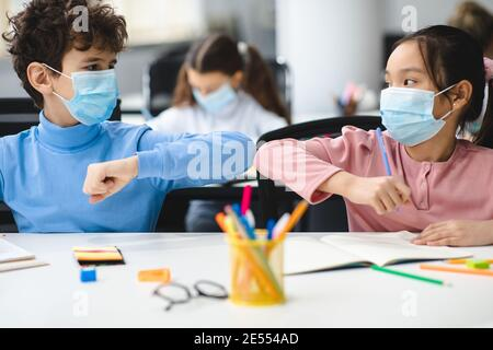 Divers élèves portant un masque facial saluant et en butant les coudes