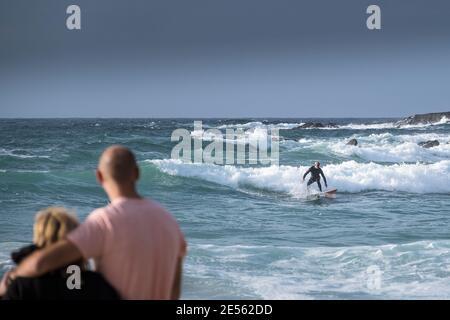 Vacanciers observant un surfeur solitaire qui fait une vague près des rochers à Fistral, à Newquay, dans les Cornouailles.