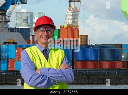 Homme souriant debout près du terminal des conteneurs. L'employé qui supervise le chargement du conteneur sur le Dock. Expédition du conteneur. Contexte logistique et transport.