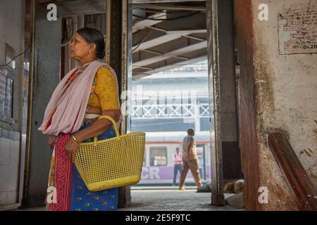 Après avoir débarqué d'un train de banlieue, une femme au foyer de Mumbai quitte Chhatrapati Shivaji Maharaj Terminus à Mumbai, la gare la plus fréquentée de la ville