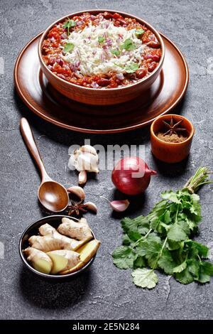 Rajala de haricots rouges Rajma, curry de haricots rouges, avec du riz dans un bol en argile sur une table en béton avec des ingrédients, vue verticale d'en haut