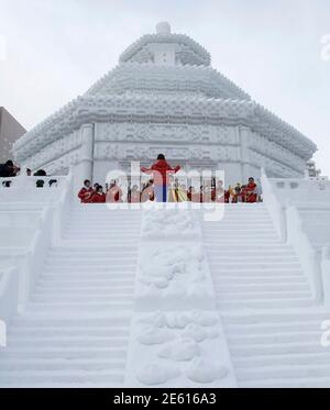 Children perform music atop a snow sculpture of China's Temple of Heaven during a ceremony to mark the start of the 62nd Sapporo snow festival in Sapporo, on Japan's northern island of Hokkaido February 7, 2011. About 250 snow and ice sculptures are exhibited in the one of Japan's popular winter events which is held until Feb 13. REUTERS/Yuriko Nakao (JAPAN - Tags: SOCIETY IMAGES OF THE DAY) Banque D'Images