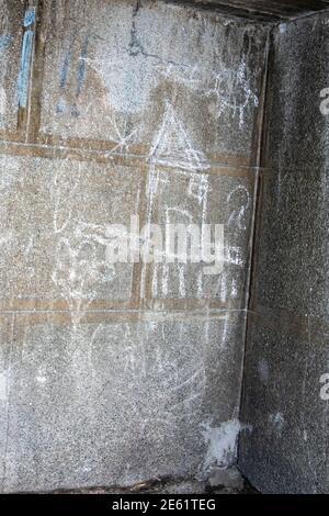 Dessin de craie blanche pour enfants d'une maison et du soleil sur un mur extérieur en béton gris