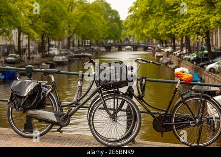 Amsterdam, Hollande 05-15-2010: Les vélos classiques de style ancien sont enchaînés aux rails métalliques de l'un des ponts au-dessus du célèbre réseau de canaux d'Amsterdam