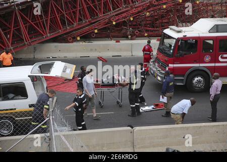 Les ambulanciers paramédicaux assistent à un passager blessé après avoir été pris dans un taxi après qu'un pont s'est effondré sur l'autoroute M1 près d'une rampe d'accès très fréquentée menant à Sandton, Afrique du Sud le 14 octobre 2015. Une personne a été tuée et 17 autres ont été blessées lorsqu'un pont s'est effondré mercredi au-dessus de l'autoroute principale de Johannesburg, ont déclaré les services d'urgence locaux. L'épave du pont métallique rouge s'est étendue sur l'autoroute M1 de Johannesburg, à proximité d'une rampe d'accès très fréquentée menant au quartier financier de Sandton, où se trouve la bourse, ce qui a provoqué un trafic de grande affluence. REUTERS/Siphiwe Sibeko