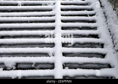 La neige blanche et fraîche repose sur une grille métallique.