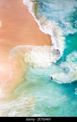 Vue d'en haut, vue aérienne stupéfiante d'une personne se relaxant sur une belle plage baignée par une mer turquoise au coucher du soleil. Plage de Kelingking, Nusa Penida