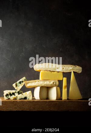 Différents fromages coupés sur bois placés sur une table en bois