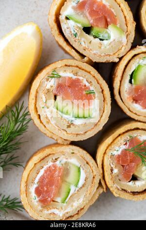Crêpe avec saumon, concombre et fromage à la crème sur une assiette, vue du dessus
