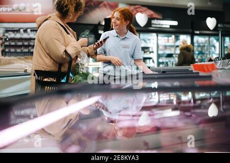 Une cliente qui demande à un employé de supermarché de l'aide pour trouver un produit alimentaire. Femme tenant son téléphone mobile et demandant de l'aide à une épicerie femelle e