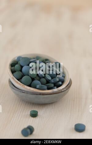 Spiruline algue vert en comprimés dans des tasses rondes en céramique sur un fond en bois clair..Suppléments diététiques.Super nourriture. Algue biologique saine.saine