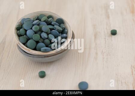 Spiruline algue vert en comprimés dans des tasses rondes en céramique sur un fond de bois clair..Suppléments diététiques.Super nourriture. Algues biologiques saines