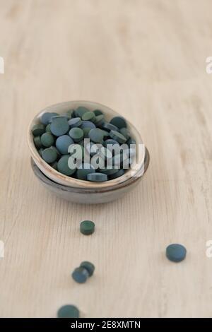 Spiruline algue vert en comprimés dans des tasses rondes en céramique sur un fond de merde en bois..Suppléments diététiques.Super nourriture. Algue biologique saine.saine