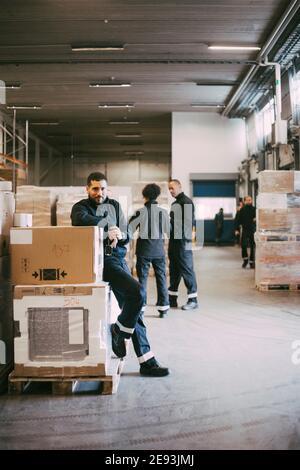 Homme d'affaires s'appuyant sur des conteneurs de boîtes dans l'entrepôt