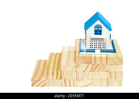 Doigts monter sur des blocs de bois à la maison miniature sur bois sur un fond blanc.le concept de croissance dans les affaires. Prêt de maison financière