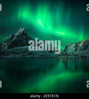 Aurores boréales sur les îles Lofoten en Norvège. Ciel étoilé en hiver. Vue sur les montagnes et Hamnoy depuis le port de Reine.
