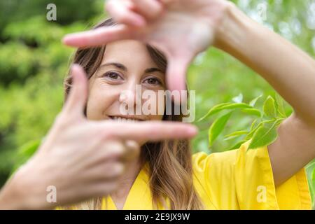 Gros plan d'une jeune femme souriante, en train de cadrer son visage avec ses mains comme autoportrait. Elle est dans la nature. Espace pour le texte.