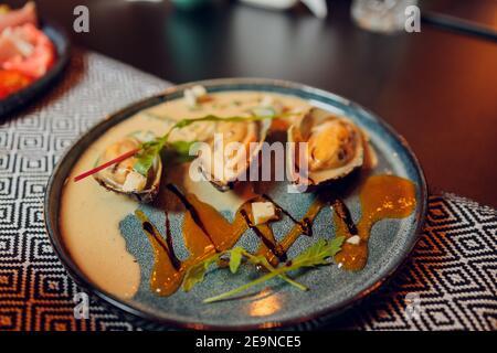 Grande assiette de moules cuites dans de la sauce tomate avec de l'ail, du persil et du citron. Espace libre pour votre texte