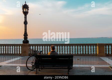 Cadix, Espagne - 09 septembre 2018 : un homme contemplant un beau coucher de soleil assis sur un banc en face de la mer, sur la promenade de Cadix, Andalousie,