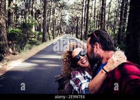 Un couple de jeunes adultes heureux avec amour et amitié profitez de la route et de la randonnée dans la forêt de bois de la nature - selfie et femme sourire huggi
