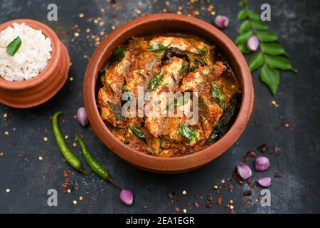 Vue de dessus Sardine poisson curry femme épicée à la main prendre Kerala poisson curry riz Inde, nourriture indienne piment rouge, feuille de curry. Cuisine asiatique. Délicieux épicé