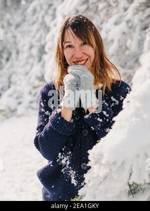 Portrait d'une belle femme parmi des arbres enneigés en forêt d'hiver. Femme souriante posant par beau temps d'hiver