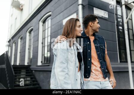 Les amoureux portent le style décontracté regardant sur le côté tout en se tenant devant un bâtiment flou. Couple amoureux dans la ville. Loveston urbain