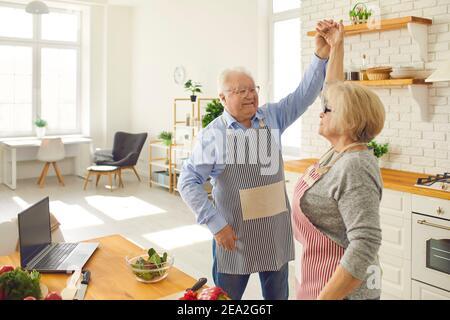 Une femme aîée heureuse dansant avec un mari affectueux et mature dans la cuisine tout en cuisinant le dîner.