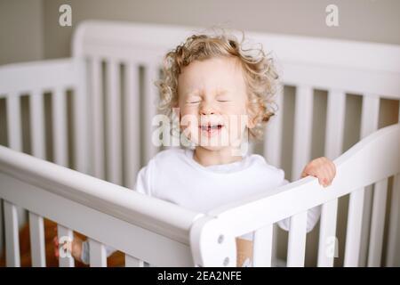 Un adorable bébé qui pleure dans un lit de bébé dans la chambre des enfants à la maison. Drôle de petit garçon avec des cheveux blonds bouclés criant à son lit. Horrible deux tout-petits