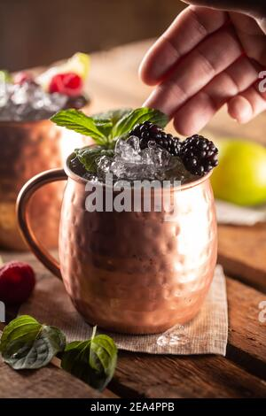 Le cocktail de vodka Moscou Berry Mule est une longue boisson avec du jus de citron vert frais, de la bière au gingembre et des baies.