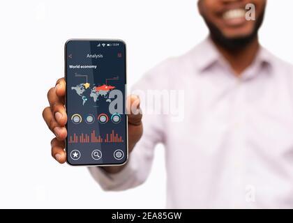 Smartphone Black Man Holding méconnaissable avec l'application World Economy Analysis À l'écran