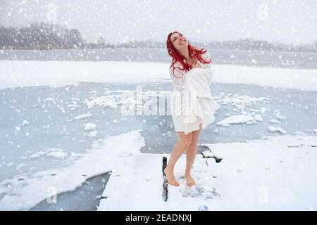 Femme heureuse durcissement et natation d'hiver concept. Femme pieds nus profitant d'un temps froid et enneigé sur un lac glacé