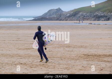 Un surfeur transportant sa planche de surf et traversant Crantock Beach à Newquay, dans les Cornouailles.