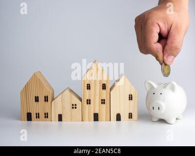 Une maison en bois modèle et une main d'homme tenant une pièce de monnaie sur un fond blanc. Concept d'entreprise de logement.