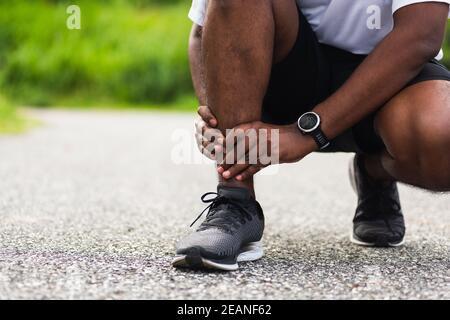 sport coureur homme utiliser les mains joint tenir la douleur de jambe parce que de la cheville tordue brisée pendant la course