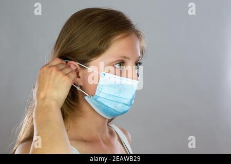Jeune femme blonde fixant un masque chirurgical à son visage