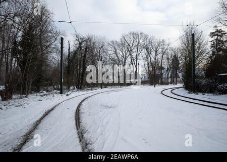 Vue extérieure ensoleillée sur la voie ferrée recouverte de neige en hiver.