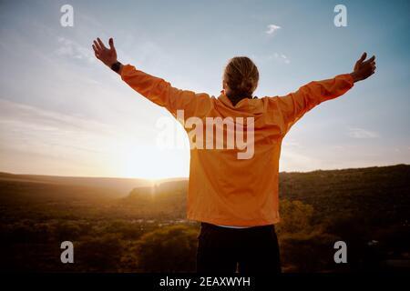 Vue arrière d'un jeune homme debout sur la montagne avec étiré les bras se détendus après une course matinale dans la nature