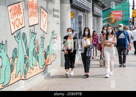 Les gens portent des masques au centre-ville de Toronto pendant la pandémie COVID-19.