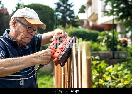 Ponceuse dans les mains. Homme senior sablant une clôture en bois dans le jardin. Ancien menuisier utilisant un outil de travail électrique