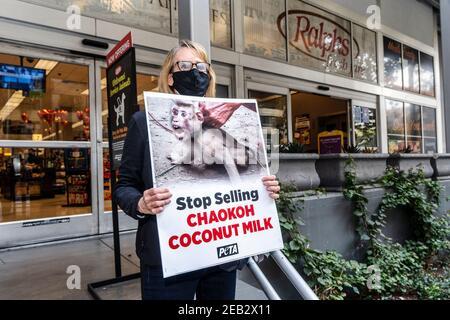Los Angeles, États-Unis. 11 février 2021. L'activiste du PETA tient un écriteau lors d'une manifestation contre la marque Chakoh en Thaïlande pour avoir soi-disant forcé des singes à grimper sur des arbres pour collecter des noix de coco et les garder dans des conditions cruelles. Les principaux détaillants américains, comme Costco et Target, ont cessé de vendre du lait de coco Chaokoh en raison d'allégations de travail forcé des singes. Crédit : SOPA Images Limited/Alamy Live News