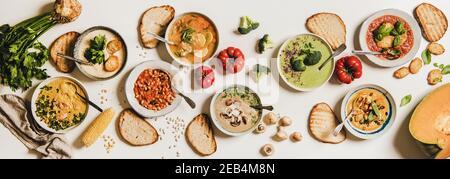 Assiette de soupe maison crémeuse végétarienne dans des assiettes avec tranches de pain sur fond blanc de table, vue du dessus. Automne l'hiver, soupes végétaliennes crémeuses, menu végétarien, concept de cuisine de confort