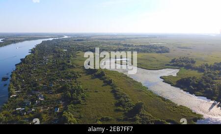 Un drone survole une rivière de couleur bleue entourée de tournieaux Village local avec divers bâtiments et habitat des marais et des marais Avec une nouvelle édition de Common Re