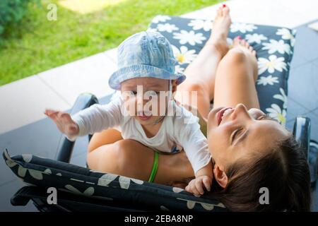 Jolie maman aimante essayant d'apaiser le bébé rouge cramoisi et de se débarrasser de la peur de bébé en la tenant dans les bras de mère, en embrassant et en souriant avec joie