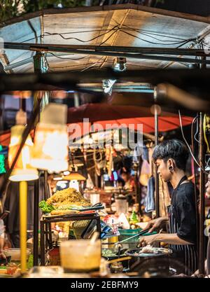 Un cuisinier prépare des plats à base de nouilles dans un plat au marché nocturne de Patong à Bangkok, en Thaïlande.
