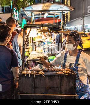 Un cuisinier prépare des brochettes de viande grillée dans un restaurant au marché nocturne de Patong à Bangkok, en Thaïlande.