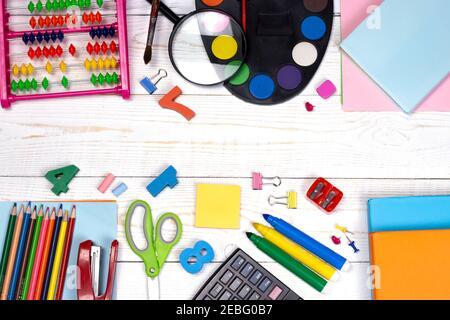 Composition de la pose à plat de retour à l'école. Fournitures scolaires, crayons, peintures, ciseaux, loupe et livres de couleur, sur la table blanche avec un photocopieur