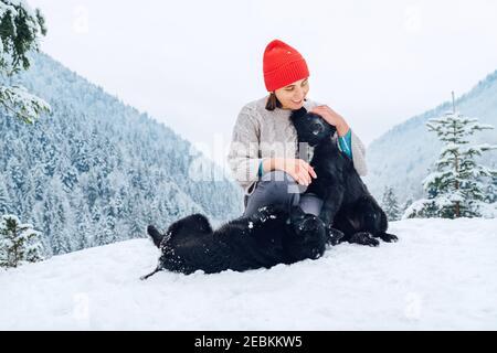 Une jeune femme en vêtements chauds marchant ses 2 chiens en montagne enneigée en plein air. Les femmes rient, s'embrasent et jouent avec les animaux de compagnie. L'homme et les animaux de compagnie hiver mer